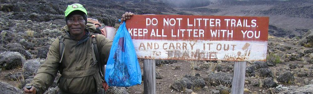 "SENE mountain guide picking up litter on Kilimanjaro next to a sign:""keep all litter with you"""
