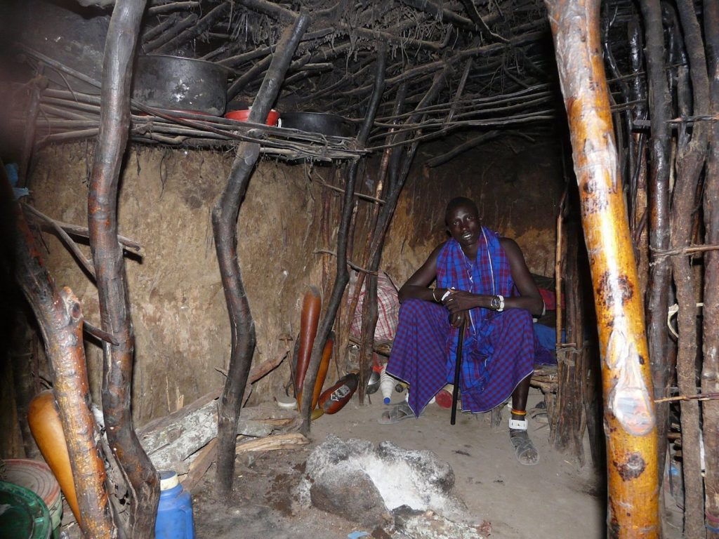 Maasai in his boma house by Rich Clampitt