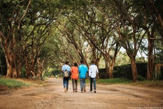 Tanzania teenagers walking under African trees